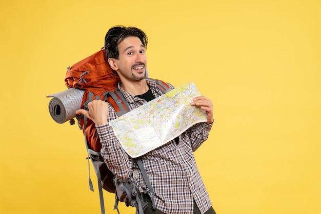 Vista frontale giovane maschio che va a fare un'escursione con lo zaino che tiene la mappa su sfondo giallo compagnia viaggio aria natura campus foresta colore