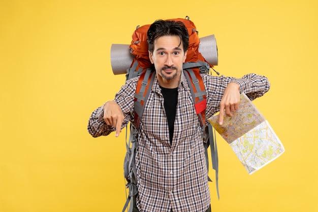Vista frontale giovane maschio che va a fare un'escursione con lo zaino che tiene la mappa su sfondo giallo compagnia viaggio aria natura campus foresta colori