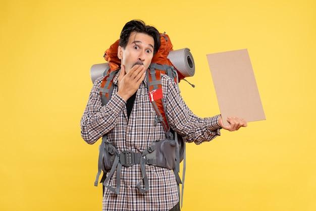 Vista frontale giovane maschio che va in escursionismo con zaino sullo sfondo giallo colore foresta natura campus emozioni viaggio aereo emotions