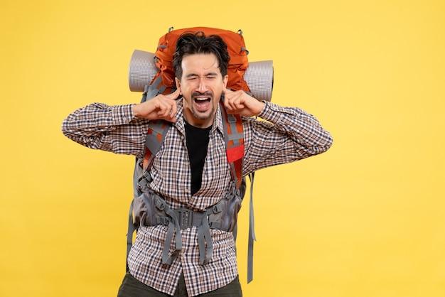 Вид спереди молодого мужчины, идущего в поход с рюкзаком, закрывающим уши на желтом фоне, цвет горного кампуса, человеческий рост, турист