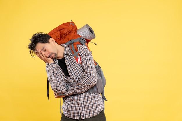 Вид спереди молодой мужчина, идущий в поход с рюкзаком, разочарованный на желтом фоне, человеческий кампус, высота горы, туристическая поездка