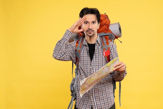 黄色の背景に会社旅行の空気自然の森の色に地図を持ってバックパックを持ってハイキングに行く正面の若い男性