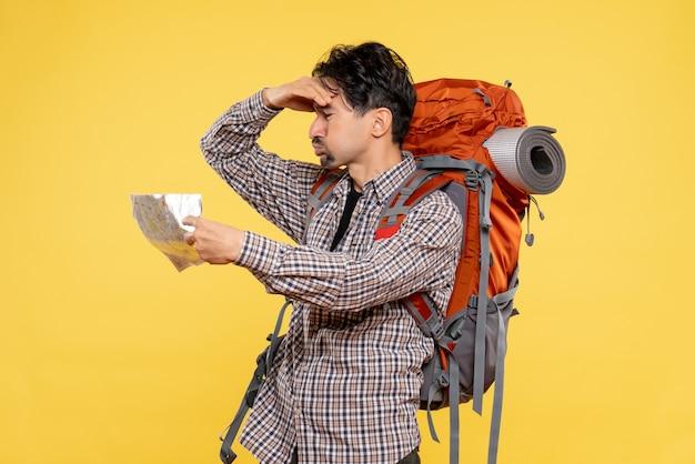 黄色の背景に会社旅行の自然の森の色の空気に地図を観察するバックパックを持ってハイキングに行く正面の若い男性