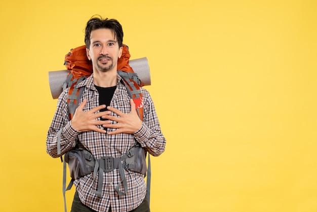 黄色の背景に人間の色の旅行キャンパス観光山の高さにバックパックを持ってハイキングに行く正面の若い男性