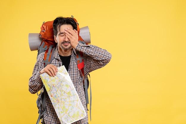 黄色の背景にバックパックを持ってハイキングに行く若い男性の正面図、自然キャンパスカラーの空中旅行地図感情