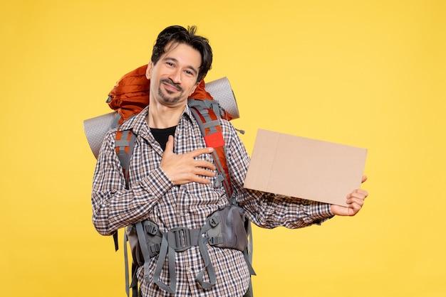 黄色の背景にバックパックを持ってハイキングに行く正面図の若い男性地図色会社旅行キャンパス空気森自然