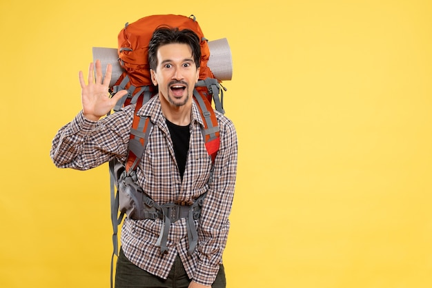 黄色の背景に観光山の人間の色の高さのキャンパスでバックパックを持ってハイキングに行く正面の若い男性
