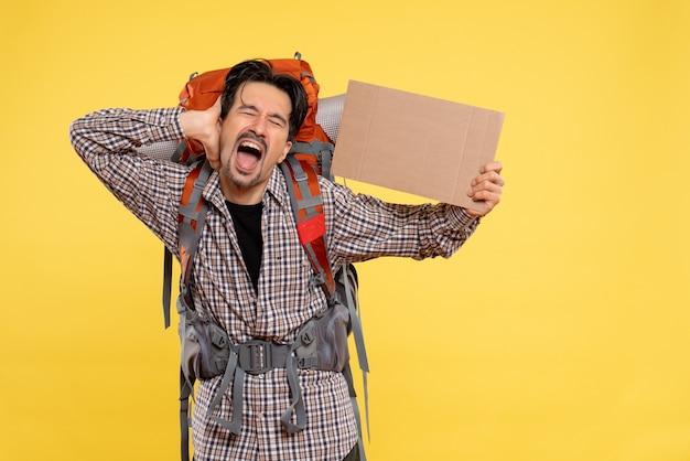 黄色の背景色の森キャンパス感情空気旅行自然にバックパックを持ってハイキングに行く正面の若い男性