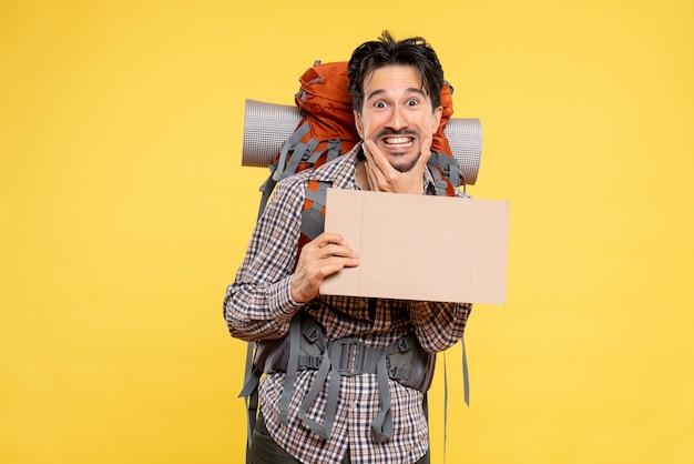 黄色のバックパックでハイキングに行く若い男性の正面図