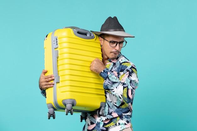 休暇に行くと水色のスペースに彼の黄色いバッグを保持している正面図若い男性