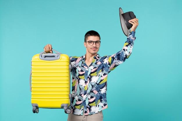 休暇に行くと青い机の上に彼の黄色いバッグを持って正面図若い男性