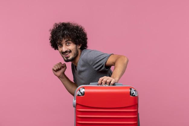 ピンクのスペースに彼の赤いバッグを持って休暇に行く若い男性の正面図