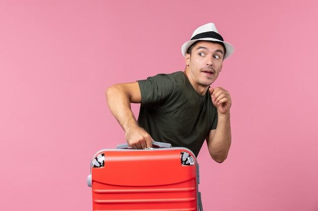 ピンクのスペースに赤いバッグを持って休暇に行く若い男性の正面図