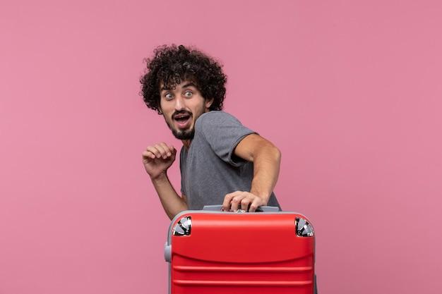 Giovane maschio di vista frontale che va in vacanza con la sua borsa rossa sullo spazio rosa