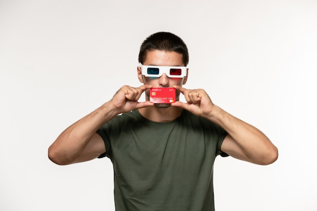 Giovane maschio di vista frontale in maglietta verde che tiene la carta di credito in occhiali da sole d sul film da parete bianco film cinema solitario maschio
