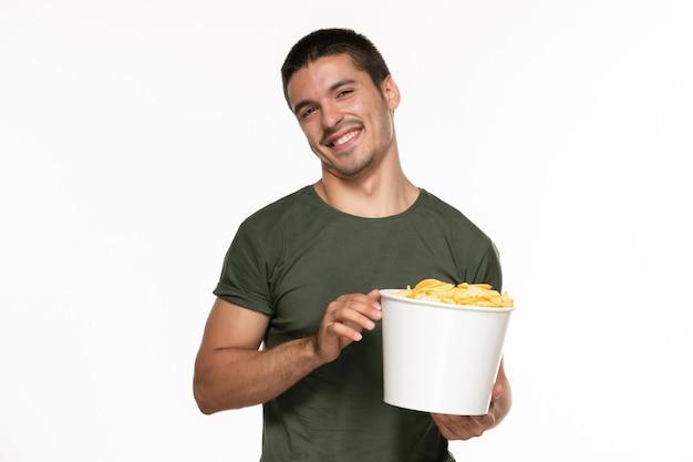 Giovane maschio di vista frontale in canestro della tenuta della maglietta verde con le patatine fritte e sorridente sul cinema di film di film di divertimento solitario della parete bianca