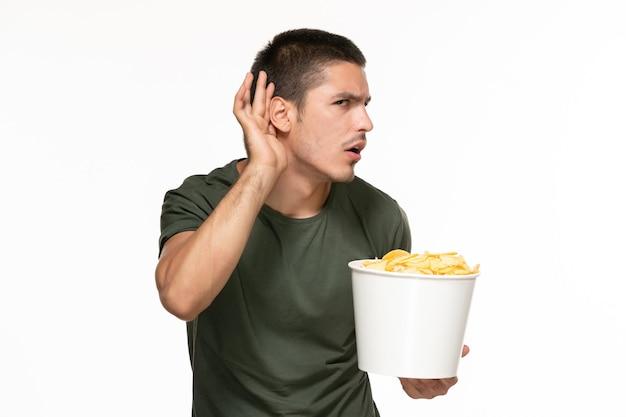 Giovane maschio di vista frontale in canestro della tenuta della maglietta verde con le patatine fritte e che prova a sentire sul cinema di film di film di godimento solitario della parete bianca