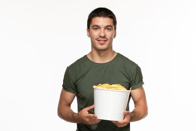 Giovane maschio di vista frontale nel canestro della tenuta della maglietta verde con le patatine fritte sul cinema di film di godimento solitario del fondo bianco