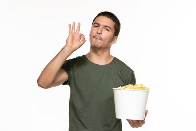 Giovane maschio di vista frontale in canestro della tenuta della maglietta verde con le patatine fritte sul cinema di film di film di godimento solitario della parete bianca