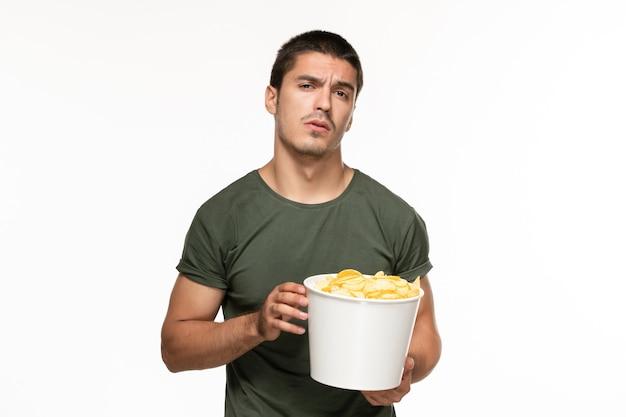 Giovane maschio di vista frontale in canestro della tenuta della maglietta verde con le patatine fritte sul cinema di film di godimento di film solitario della parete bianca