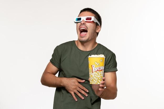 Giovane maschio di vista frontale in maglietta verde che tiene popcorn in occhiali da sole d guardando film su film di superficie bianca chiara film solitario cinema maschile