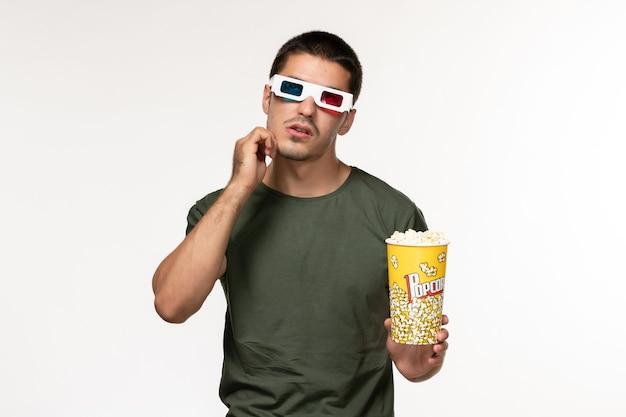 Giovane maschio di vista frontale in maglietta verde che tiene popcorn in occhiali da sole d guardando film che pensa sui film maschii del cinema solitario del film della parete bianca