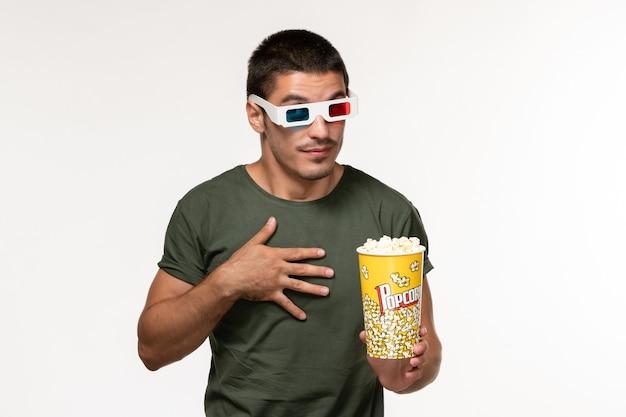 Giovane maschio di vista frontale in maglietta verde che tiene popcorn in occhiali da sole d che guarda film sui film maschii del cinema solitario del film della scrivania bianca