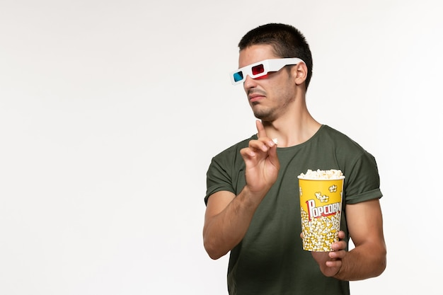 Front view young male in green t-shirt holding popcorn in -d sunglasses watching movie on white wall film lonely cinema male movie