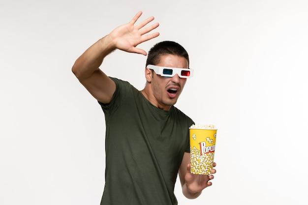 Giovane maschio di vista frontale in maglietta verde che tiene popcorn in occhiali da sole d che guarda film sui film maschii del cinema solitario del film della parete bianca