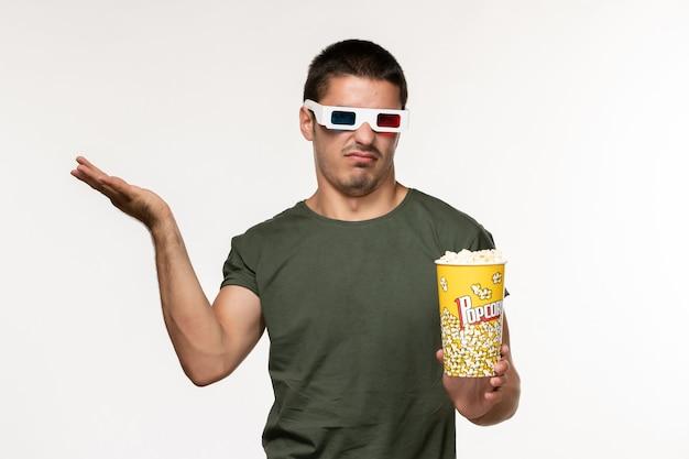Giovane maschio di vista frontale in maglietta verde che tiene popcorn in occhiali da sole d guardando film su film di cinema solitario film di parete bianca