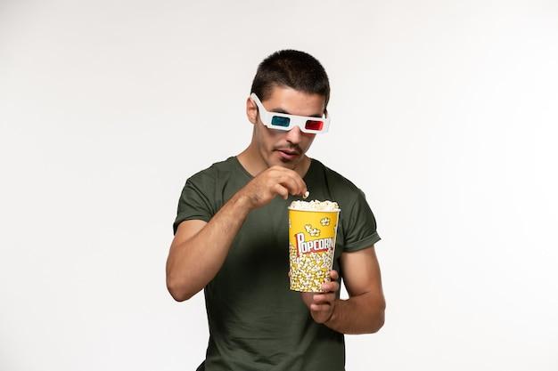 Giovane maschio di vista frontale in maglietta verde che tiene popcorn in occhiali da sole d sui film maschii del cinema solitario del film della parete bianca