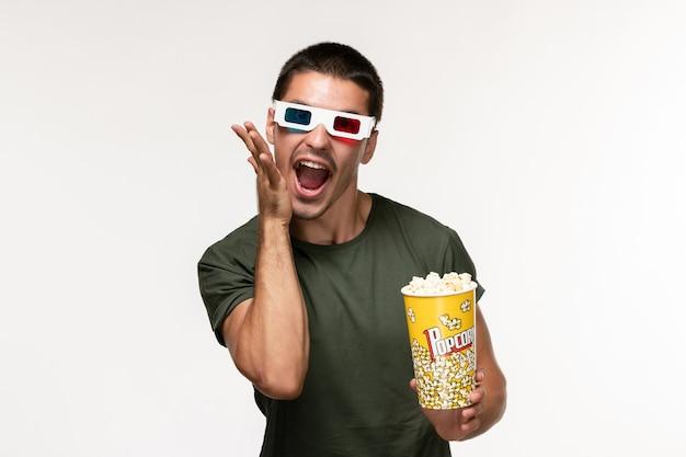 Giovane maschio di vista frontale in maglietta verde che tiene il pacchetto del popcorn in occhiali da sole d sul film maschio del cinema solitario della pellicola bianca chiara della parete