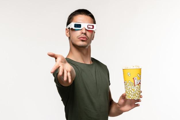 Giovane maschio di vista frontale in maglietta verde che tiene il pacchetto del popcorn in occhiali da sole d su un film maschio del cinema solitario della parete bianca