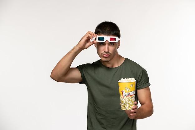 Giovane maschio di vista frontale in maglietta verde che tiene popcorn e che toglie gli occhiali da sole -d che guardano film sui film maschii del cinema solitario del film della parete bianca