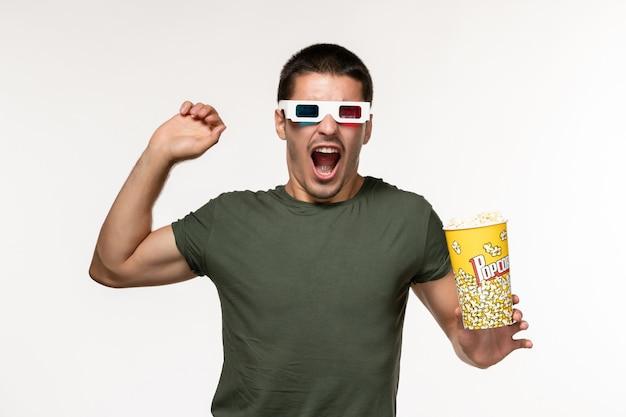 Giovane maschio di vista frontale in maglietta verde che tiene popcorn indossando occhiali da sole d e che flette sul cinema solitario di pellicola bianca della parete