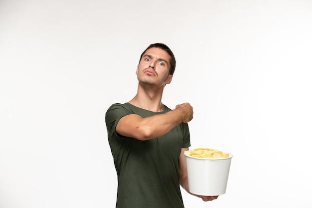 Giovane maschio di vista frontale in maglietta verde che tiene le patatine fritte sulla persona solitaria del cinema di film dello scrittorio bianco-chiaro