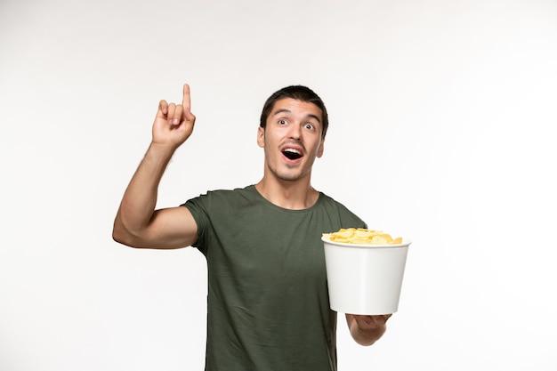 Giovane maschio di vista frontale in maglietta verde che tiene le patatine fritte sulla persona solitaria del cinema di film della pellicola bianca chiara della parete