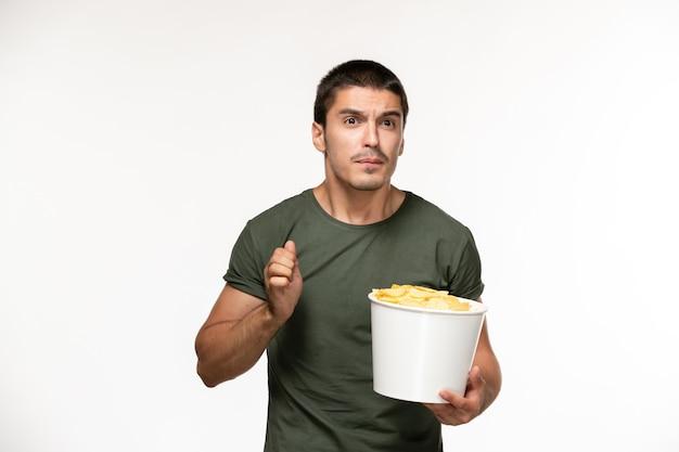 Giovane maschio di vista frontale in maglietta verde che tiene le patatine fritte su una parete bianca chiara persona solitaria film cinema