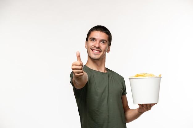 Giovane maschio di vista frontale in maglietta verde che tiene le patatine fritte che mostrano come segno sulla persona solitaria del cinema di film del film della parete bianca