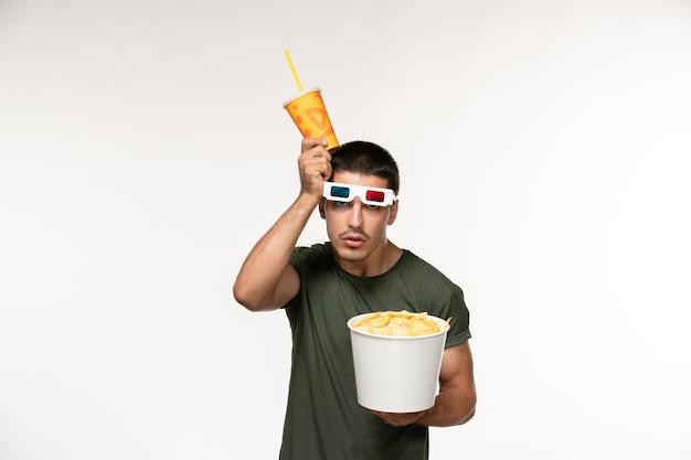 Giovane maschio di vista frontale in maglietta verde che tiene soda di patatine fritte in -d occhiali da sole sul cinema di film solitario maschio della pellicola della parete chiara