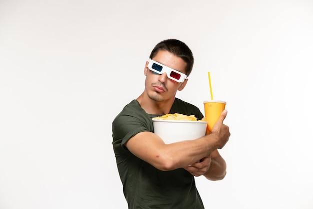 Giovane maschio di vista frontale in maglietta verde che tiene soda di patatine fritte in occhiali da sole d sul cinema di film solitario maschio della pellicola bianca chiara della parete