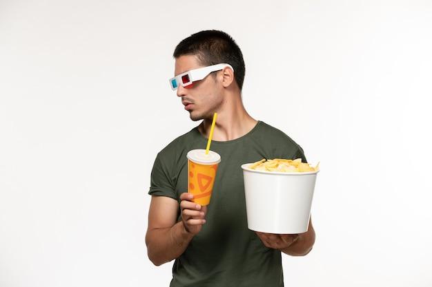 Giovane maschio di vista frontale in maglietta verde che tiene soda di patatine fritte in -d occhiali da sole sul cinema di film solitario maschio della pellicola bianca chiara della parete