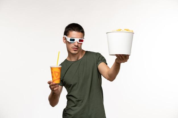 Giovane maschio di vista frontale in maglietta verde che tiene soda di patatine fritte in occhiali da sole d sul cinema di film solitario maschio del film dello scrittorio bianco