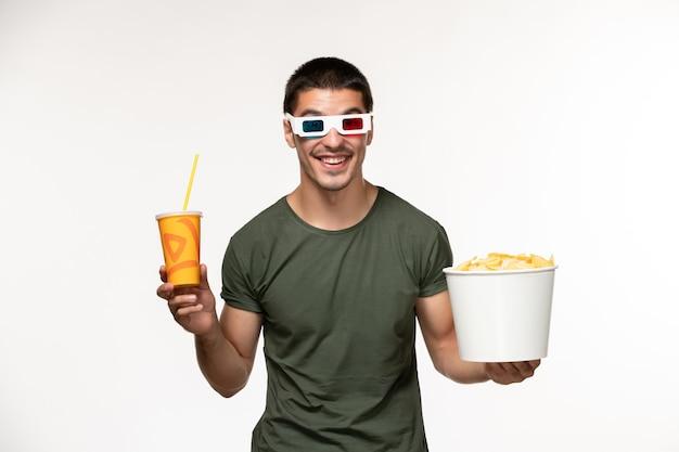 Giovane maschio di vista frontale in maglietta verde che tiene soda di patatine fritte in occhiali da sole d sul cinema di film solitario maschio della pellicola bianca della parete