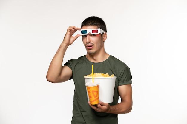 Giovane maschio di vista frontale in maglietta verde che tiene le patatine fritte e la soda in occhiali da sole d sul film solitario maschio della pellicola bianca della parete