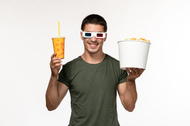 Giovane maschio di vista frontale in maglietta verde che tiene la soda delle patatine fritte in occhiali da sole di d sul cinema solitario maschio di film della pellicola bianca della parete