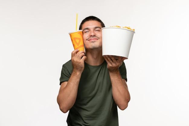 Giovane maschio di vista frontale in maglietta verde che tiene le patatine fritte e la soda sul maschio del cinema della pellicola della parete bianca solitario
