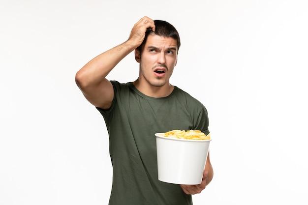 Giovane maschio di vista frontale in maglietta verde che tiene le patatine fritte e che pensa sul cinema di film solitario della parete bianca