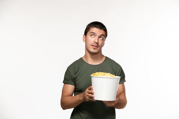 Giovane maschio di vista frontale in maglietta verde che tiene le patatine fritte e pensando sulla persona solitaria del cinema di film di film della parete bianca