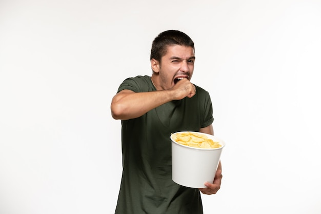 Giovane maschio di vista frontale in maglietta verde che tiene le patatine fritte che guardano film sul cinema di film di film solitario della persona della parete bianca